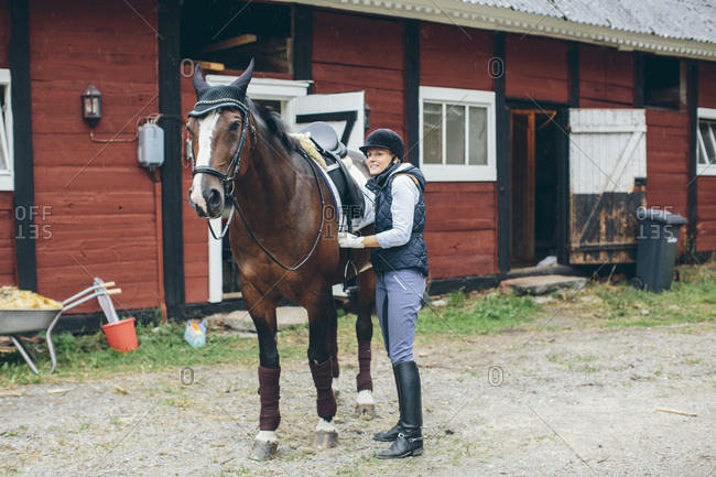 Sweden, Blekinge, Mid adult woman and horse in front of stable