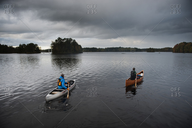 Sweden, Smaland, Men swimming in lake in boats