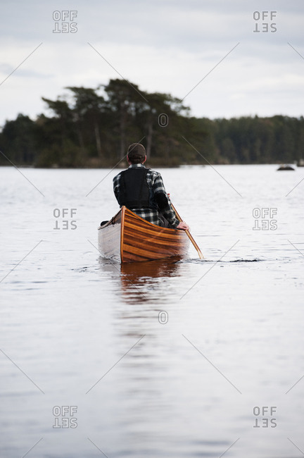 Sweden, Smaland, Man swimming in lake in boat