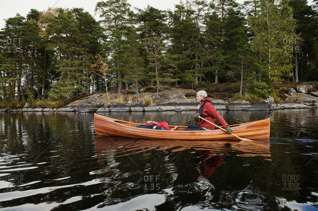 Sweden, Smaland, Man swimming in lake in boat