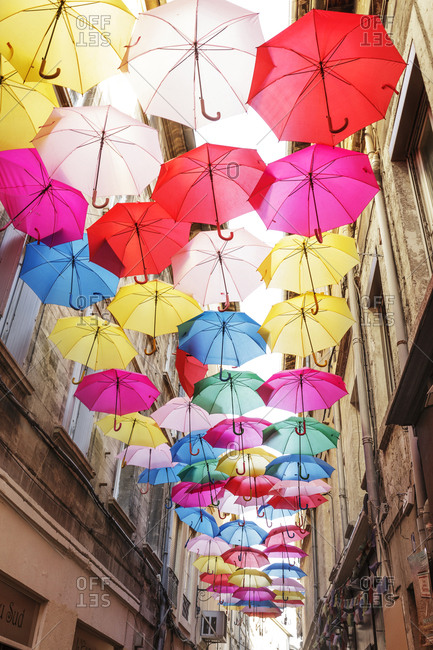 France, Avignon - November 1, 2016: Colorful umbrellas hanging over old town street