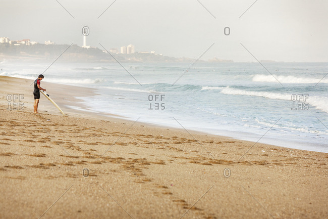 France, Biarritz - November 1, 2016: Surfer standing on beach