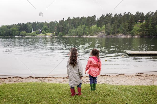 Sweden, Uppland, Roslagen, Vato, Two girls (4-5, 6-7) standing by lake shore