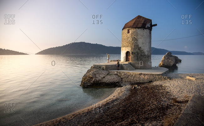 Greece, Kalamos,  - November 10, 2016: Men standing by old concrete windmill built on seashore