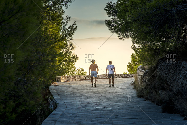 Greece, Cephalonia, Assos, Tourists walking on footpath