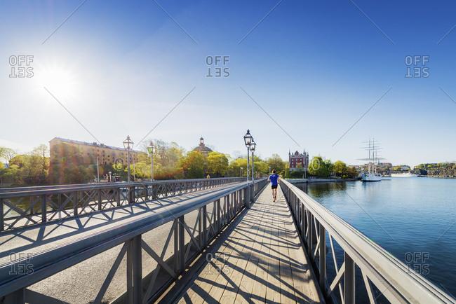 Sweden, Stockholm, Skeppsholmen, Young man running on bridge