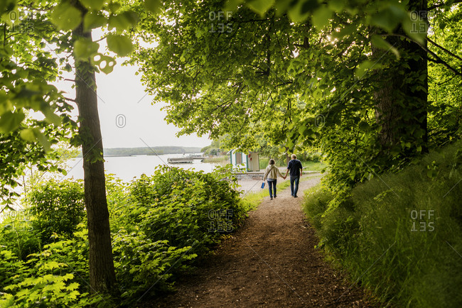 Sweden, Stockholm Archipelago, Uppland, Vaxholm, Couple walking by lake holding hands