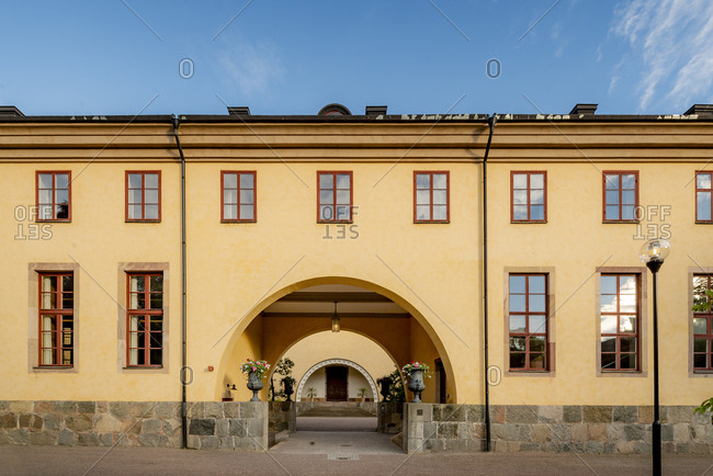 Sweden, Uppland, Uppsala, Arched entrance of yellow building in Linnean Gardens of Uppsala