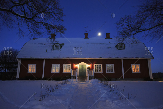 Sweden, Narke, Hasselfors, Trantorp, Illuminated facade of snowy house