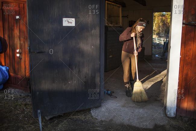 Sweden, Uppland, Faringso, Woman sweeping in barn