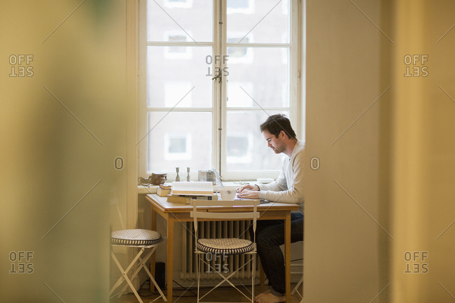 Sweden, Man using laptop at table