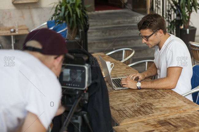 Sweden, Uppland, Man recording man using laptop at table
