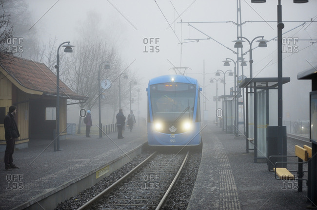 Sweden, Uppland - September 22, 2016: Train in fog entering station