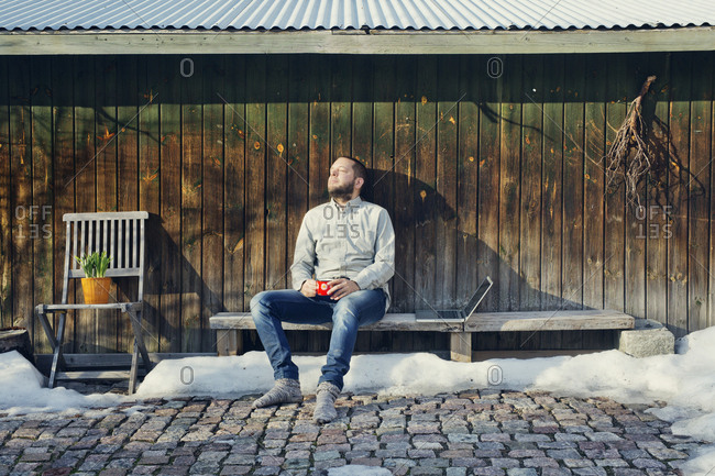 Finland, Paijat-Hame, Heinola, Mid adult man sitting on bench by wooden shed