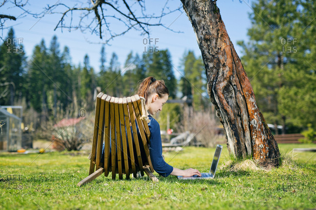 Finland, Paijat-Hame, Heinola, Mid adult woman lying down on sun lounger in garden and using laptop