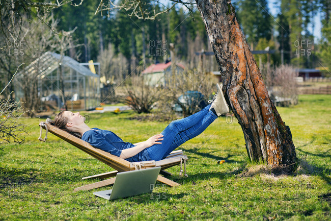 Finland, Paijat-Hame, Heinola, Mid adult woman lying down on sun lounger in garden