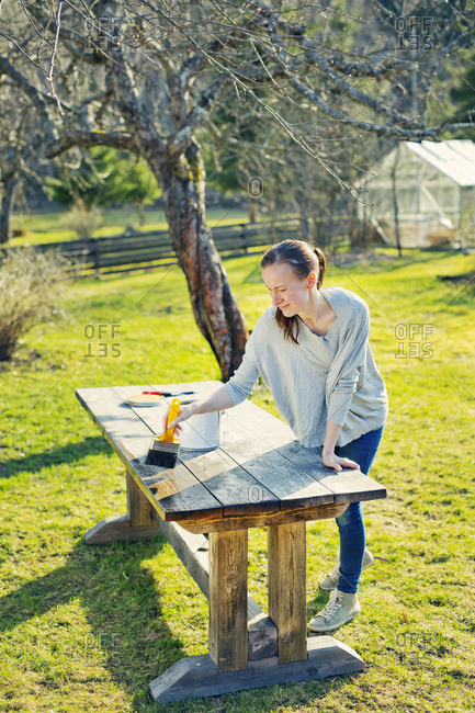 Finland, Paijat-Hame, Heinola, Mid adult woman oiling wooden table in garden