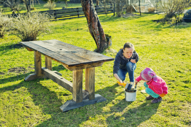Finland, Paijat-Hame, Heinola, Mother with daughter oiling wooden table in garden