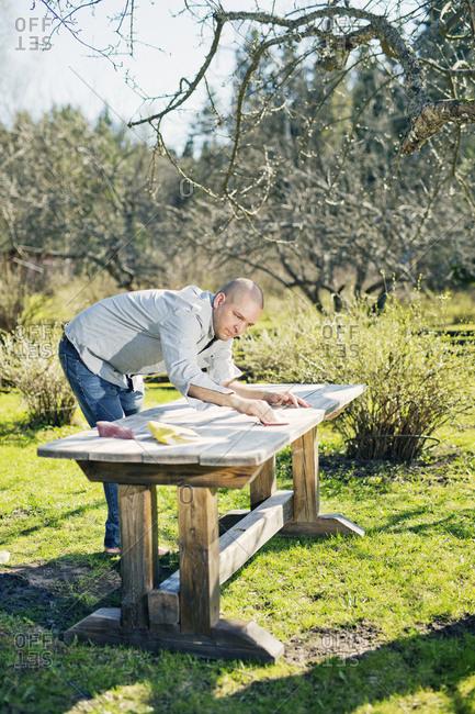 Finland, Paijat-Hame, Heinola, Mid adult man polishing wooden table in garden
