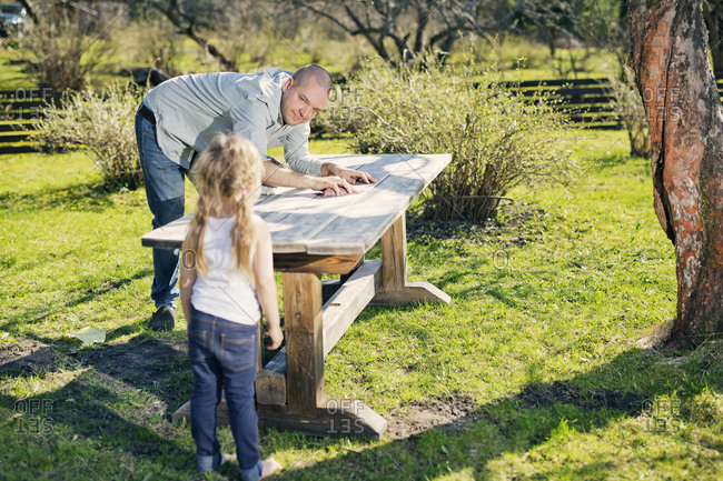 Finland, Paijat-Hame, Heinola, Father with daughter polishing wooden table in garden