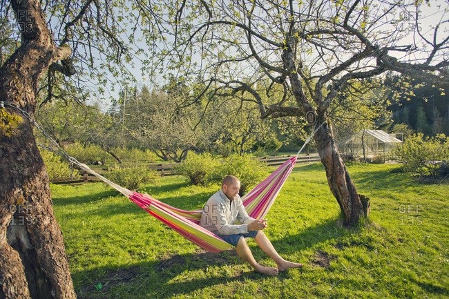Finland, Paijat-Hame, Heinola, Mid adult man sitting on hammock and using phone