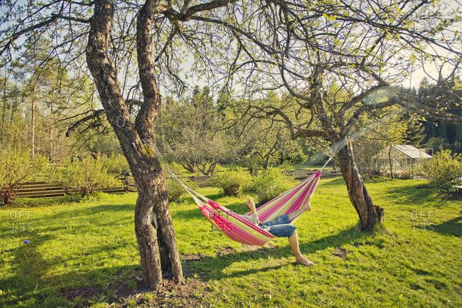 Finland, Paijat-Hame, Heinola, Mid adult man lying down on hammock