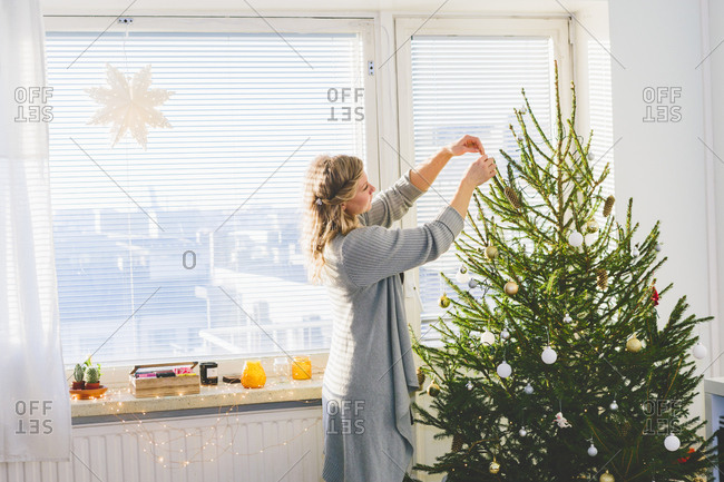 Finland, Helsinki, Woman decorating Christmas tree