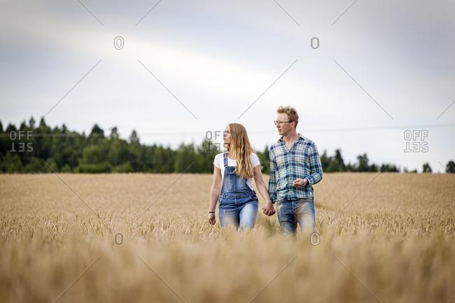 Finland, Uusimaa, Siuntio, Mid adult couple walking in wheat field