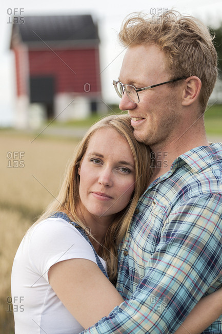 Finland, Uusimaa, Siuntio, Mid adult couple embracing in field