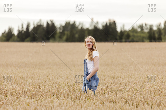 Finland, Uusimaa, Siuntio, Blonde woman standing in wheat field