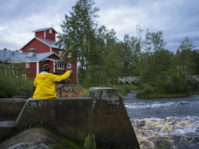 Finland, Ostrobothnia, Kruunupyy Woman sitting by river and holding handmade fishing rod