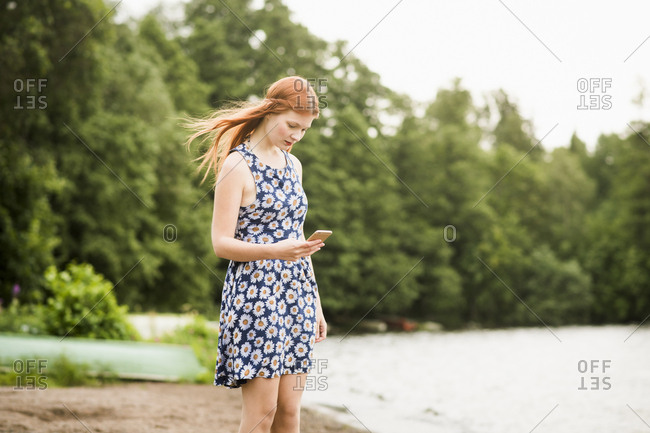 Finland, Pirkanmaa, Tampere, Woman with mobile phone standing on beach