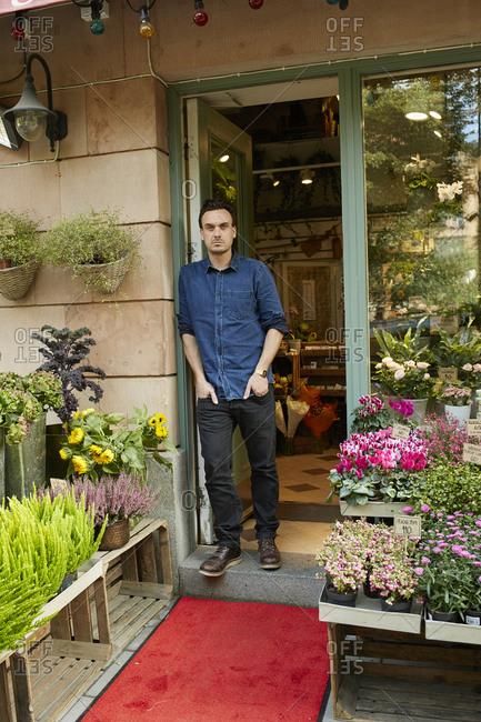 Sweden, Florist standing in front of entrance of flower shop