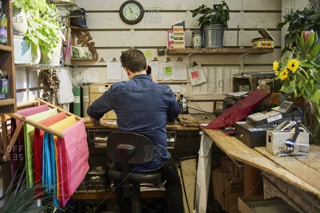 Sweden, Florist using phone in flower shop