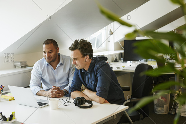 Sweden, Businessmen sitting side by side and looking on laptop in office