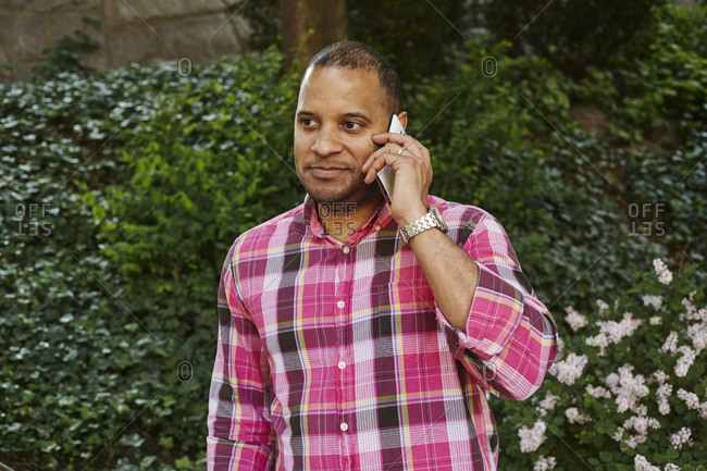 Sweden, Mature man in pink checked shirt using mobile phone