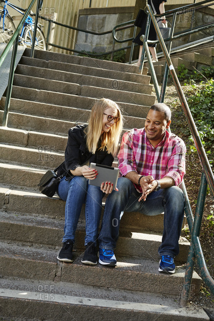 Sweden, Man and woman sitting side by side on steps and looking at digital tablet
