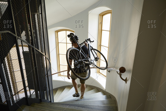 Sweden, Cyclist carrying bicycle on steps