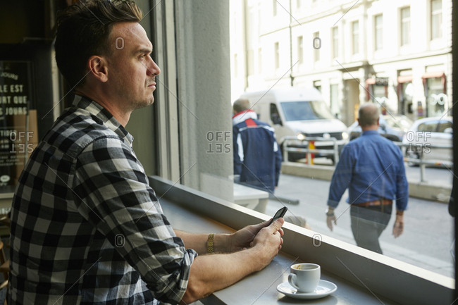 Sweden, Man holding cellphone and looking through window in cafe