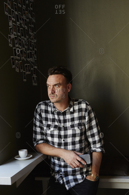 Sweden, Pensive man in cafe looking away and holding mobile phone