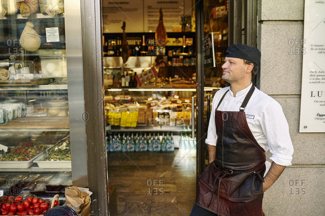 Sweden, Man in apron standing in front of store