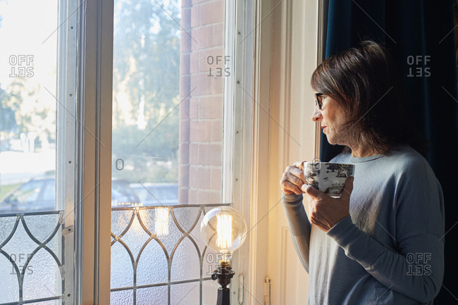 Sweden, Woman looking through window, holding coffee cup