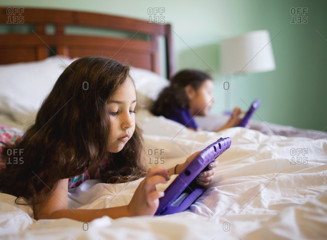 Girls using tablets while lying in bed
