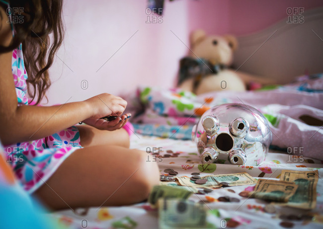 Young girl counting money from a chrome piggy bank