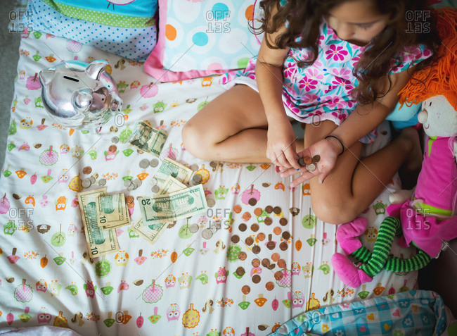 Young girl counting her piggy bank money