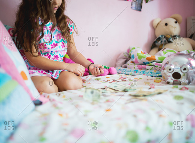 Girl counting piggy bank money on her bed