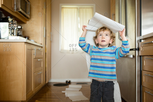 Toddler playing with paper towels in the kitchen