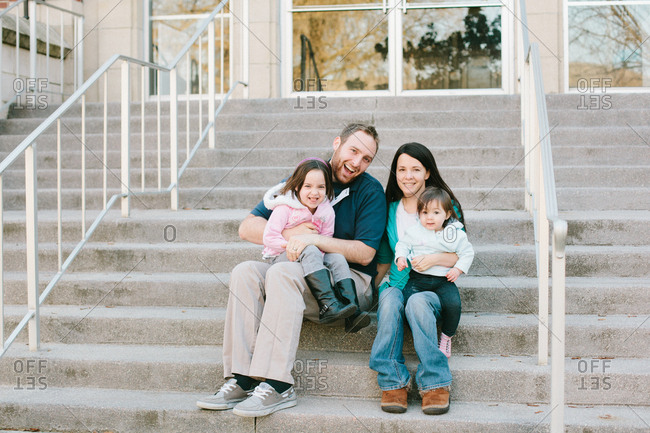 Family of four sitting on stairs in front of building
