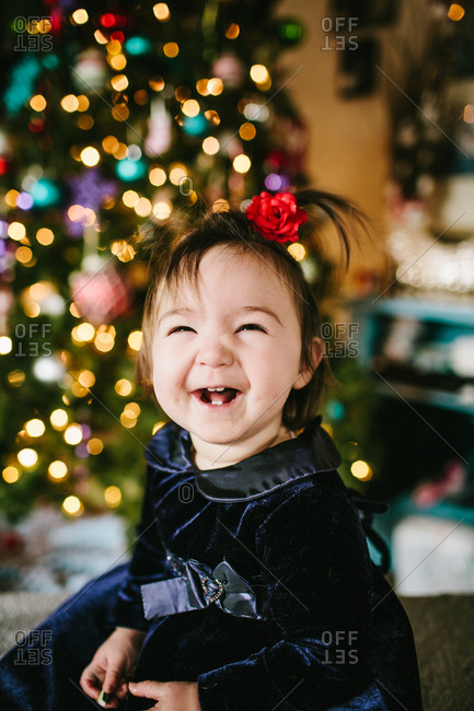 Young toddler smiling in front of a Christmas tree