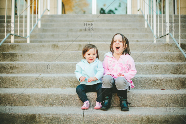 Portrait of two children laughing together on stairs